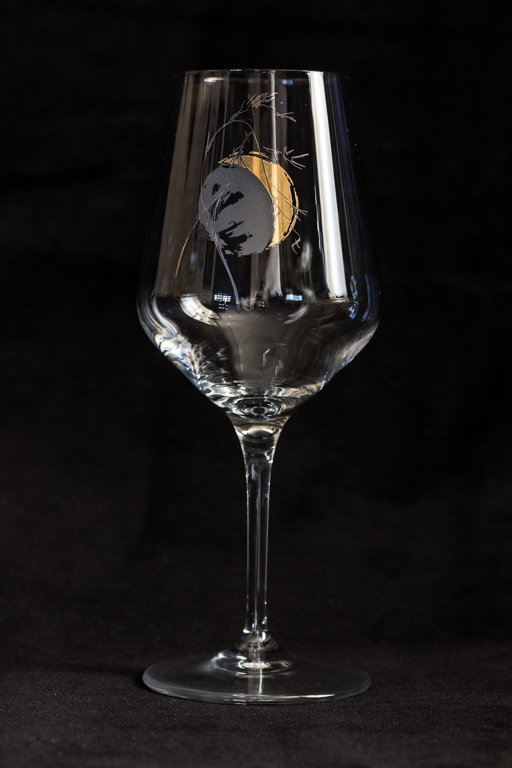 Wine glass with the moon and a blade of grass