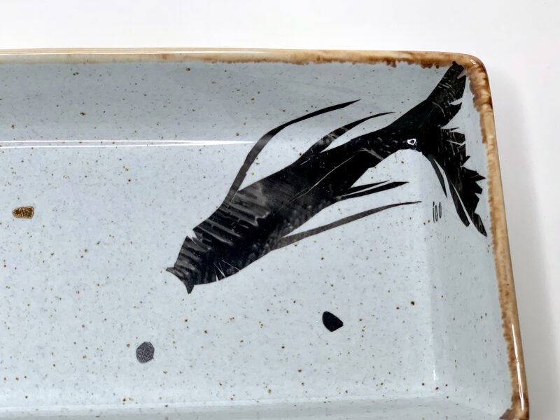 Pelēka kantaina bļodiņa ar zivs zīmējumu.